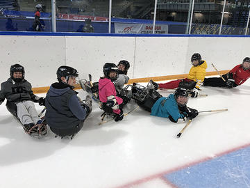 Adapted camp participants playing hockey