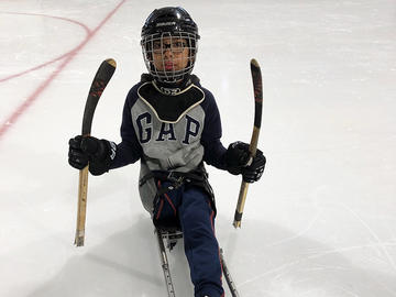 Adapted camp participant playing hockey